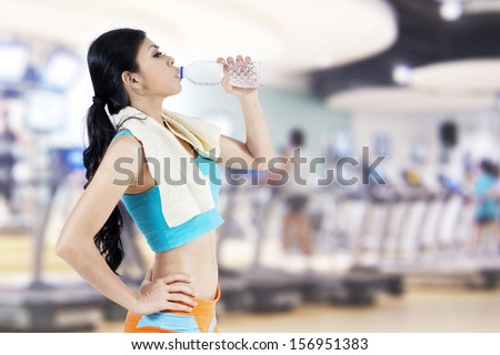 Gym woman drinking water from a bottle. Shot at fitness center - stock photo