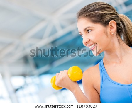 Gym woman exercising lifting free weights and smiling - stock photo