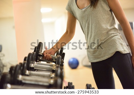Gym woman strength training lifting dumbbell weights getting ready for exercise workout. Female fitness girl exercising indoor in fitness center. Beautiful fit mixed race Asian Caucasian model. - stock photo