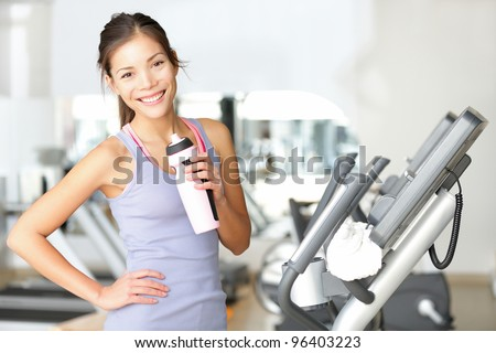 Gym woman working out drinking water smiling happy standing by moonwalker fitness machines. Beautiful fit young mixed race Caucasian / Chinese Asian female fitness model inside in fitness center. - stock photo