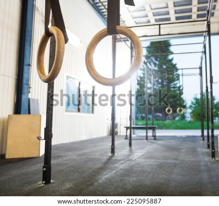Gymnastic rings hanging in gym - stock photo