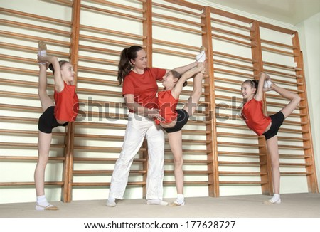 Gymnastics coch teaching little girls - stock photo
