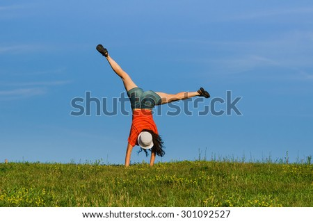 gymnastics woman doing cartwheel on nature backgrounds. motion blur effect - stock photo