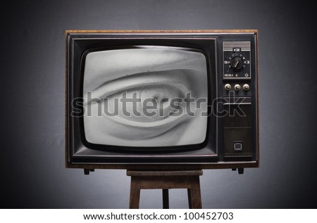 Gypsum eye looks to the old TV screen. - stock photo