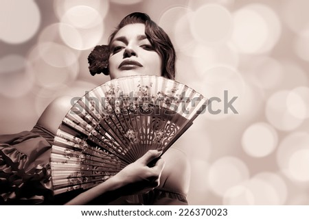 Gypsy Flamenco Festival. Beautiful Andalusian woman with carnation in hair and stylish fan. Spanish beauty. Fine Art portrait in sepia with copy space for text. - stock photo