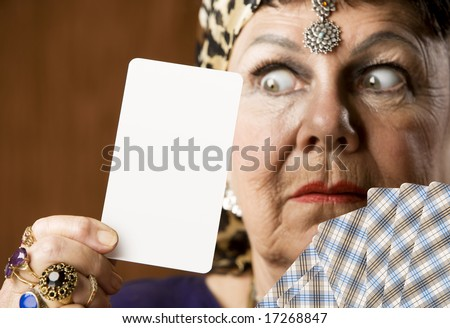 Gypsy fortune teller holding a blank tarot card - stock photo