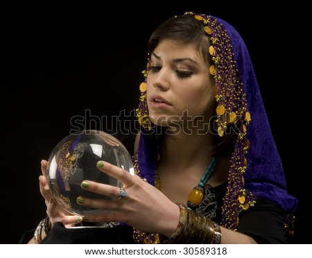 Gypsy fortune-teller uses a crystal ball to foertell the future - stock photo