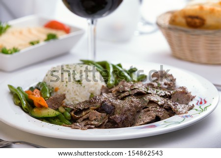 Gyro Doner garnished with rice Pilaf and vegetables partnered with hummus, pita bread and red wine - stock photo