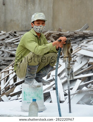 Ha Long Bay, Vietnam - April 17, 2015: Young man man working in a Ceramics factory in Ha Long Bay Vietnam surrounded by white Marble dust.  - stock photo