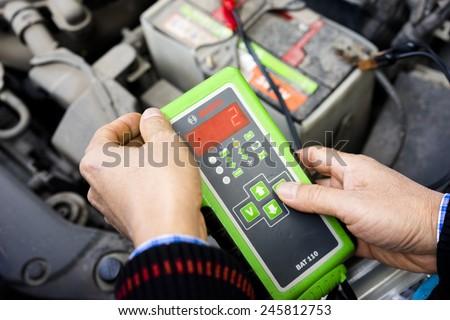 Ha Noi, Viet Nam - Dec 13, 2014: Auto mechanic uses multimeter voltmeter to check voltage level in car battery in Vietnam - stock photo