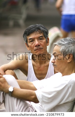 HA NOI, VIET NAM - JUNE 15, 2010: Portrait of an elderly gentleman sitting on a bench with his friend in Vietnam - stock photo