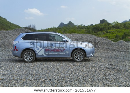 Ha Noi, Viet Nam - May 18, 2015: The Mitsubishi Outlander PHEV plug-in Hybrid CUV car running on the rocky gravel stones road in Vietnam - stock photo