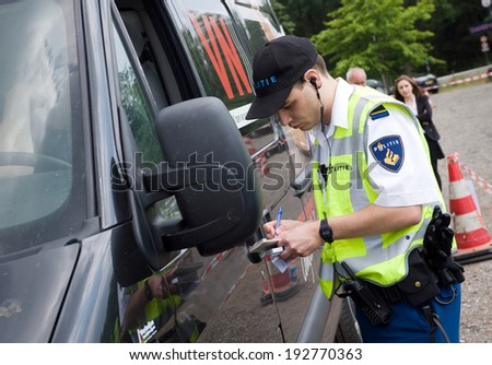 HAAKSBERGEN, NETHERLANDS - JUNE 09: A policeman is checking the driving license of a car driver during a massive traffic control, june 09, 2011 in the Netherlands - stock photo