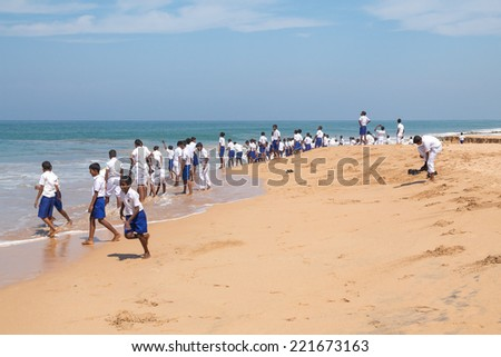 HABARADUWA, SRI LANKA - MARCH 11, 2014: Group of school kids at beach at Sea Turtle Farm and Hatchery. The center was started in 1986 and up to now they released more than 500,000 Turtles to ocean - stock photo