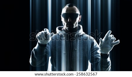 Hacker hacking, futuristic virtual keyboard, black background - stock photo