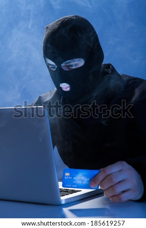 Hacker holding credit card while using laptop at table - stock photo