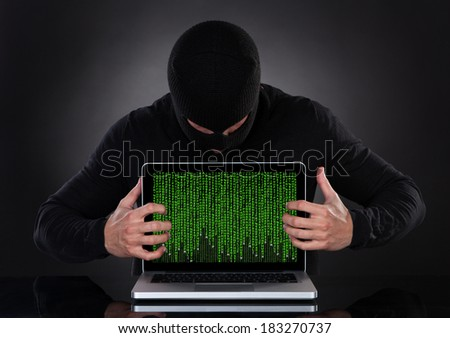 Hacker in a balaclava standing in the darkness furtively stealing data off a laptop computer or inserting spyware in an online security and risk concept - stock photo