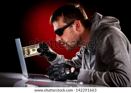 Hacker in a sunglasses with laptop and money in hand - stock photo