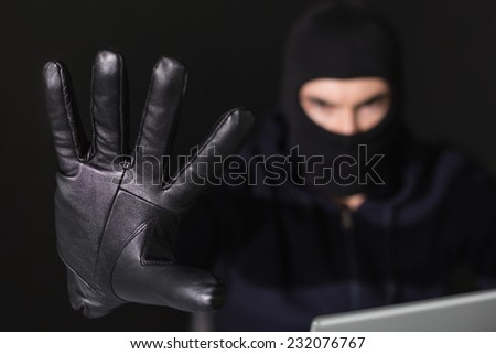 Hacker in balaclava with fingers spread out on black background - stock photo
