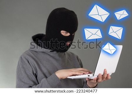 hacker in black mask stealing data from e-mail - stock photo