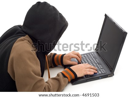 Hacker in the front of a laptop computer - stock photo