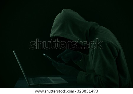 Hacker looking for password and user information using digital tablet and laptop computer - stock photo