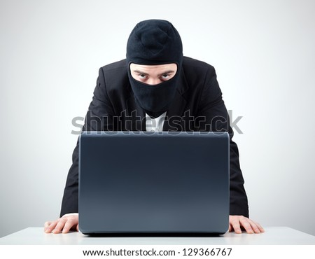 Hacker stealing information from a computer at the desk - stock photo