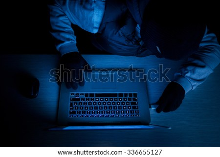 Hacker thief with laptop in darkness - stock photo