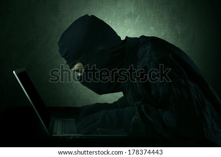 Hacker typing on a laptop and looking at computer screen - stock photo