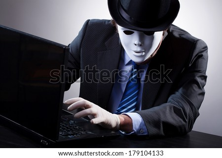 Hacker wearing a suit and mask in front of computer - stock photo
