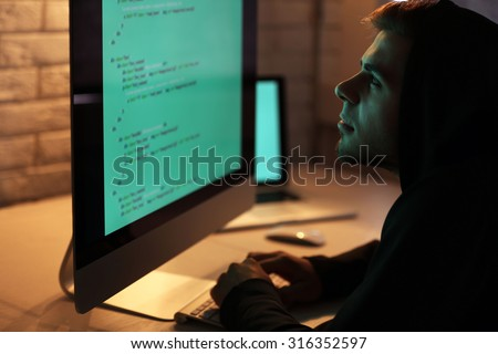 Hacker with computer and laptop  - stock photo