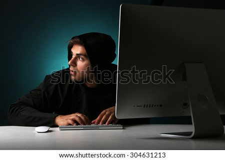 Hacker with computer on colorful dark background  - stock photo