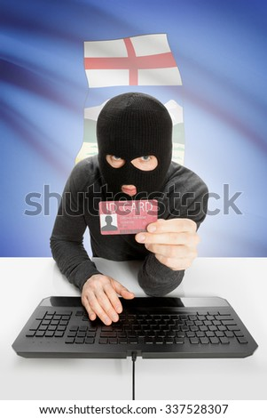 Hacker with ID card in hand and Canadian province flag on background - Alberta - stock photo