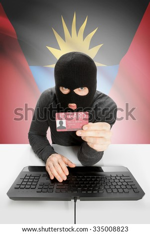Hacker with ID card in hand and flag on background - Antigua and Barbuda - stock photo