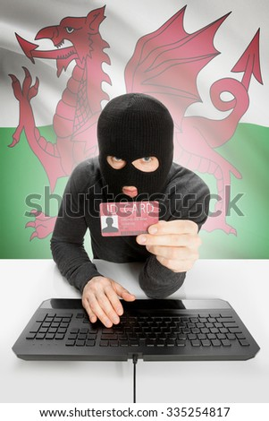 Hacker with ID card in hand and flag on background - Wales - stock photo