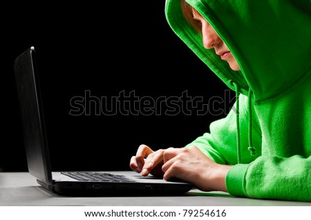 hacker. Young man with laptop is looking at screen - stock photo