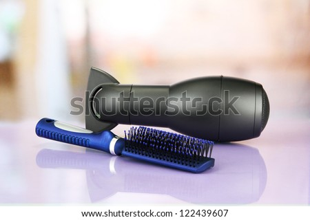 hair dryer and comb brush, on table in beauty salon - stock photo