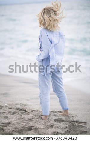 """hair in the wind. The ease of mind. Woman enjoying the sea breeze , sea and sand . Smiles , do not think of """"tomorrow"""" . - stock photo"""