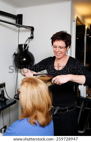 hair of a customer is brushed by hairdresser