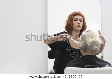 Hair stylist cutting senior woman's hair in salon - stock photo