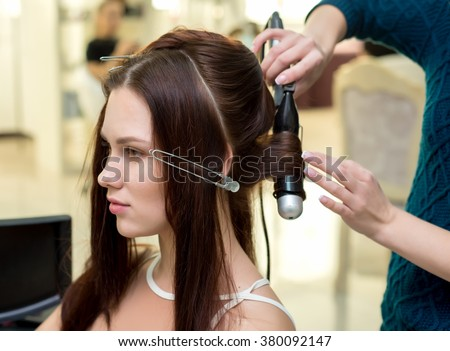 Hair stylist making ringlets to brunette woman. Hairdresser working with beautiful woman hair in hairdressing salon. Close up view of hand, curling iron and the appliance - stock photo