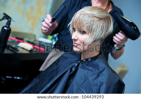 hair stylist using dryer on woman wet hair in salon - stock photo