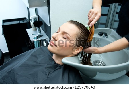 hair stylist washing and combing woman hair in salon - stock photo