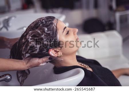 Hair stylist washing model's hair. Shampoo treatment - stock photo