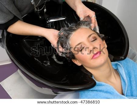 hair stylist washing woman hair with shampoo - stock photo