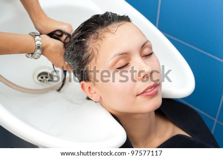 hair washing at a hairdressing salon, young caucasian brunette - stock photo