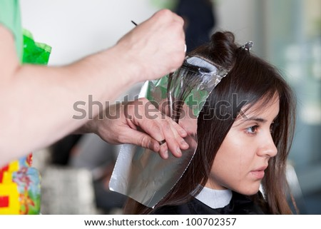 Hairdresser applying color to customer's hair. Selective focus. - stock photo