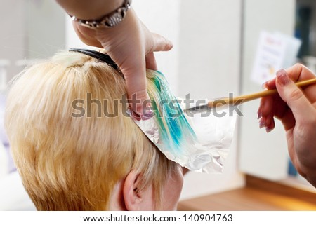 hairdresser applying hair color in a salon - stock photo