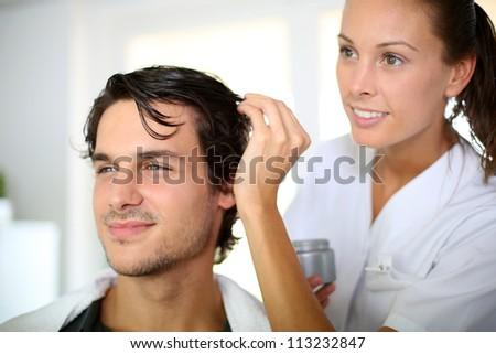 Hairdresser applying hair gel - stock photo