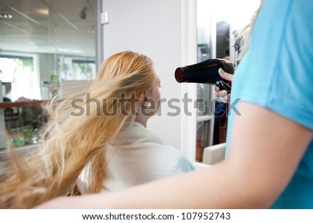 Hairdresser blow drying female customer's hair at parlor - stock photo